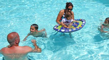 Happy family playing in emerald cove resort pool